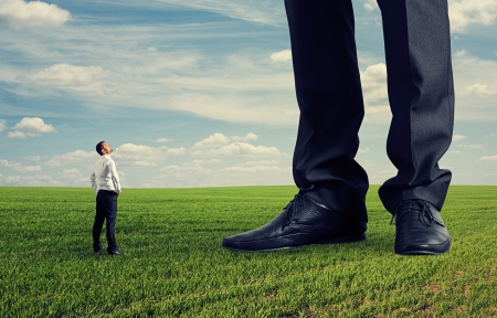 competitive business: small businessman looking at his big boss. photo on green field Stock Photo