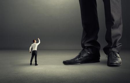 jefe enojado: hombre de negocios enojado mirando hacia arriba y muestra el puño a su gran jefe