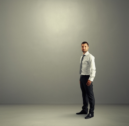 serious businessman standing in the grey room and looking at camera