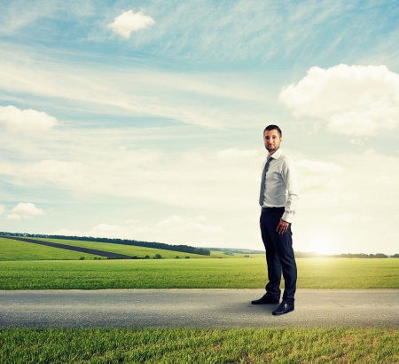 distant: serious businessman standing on the road over green field