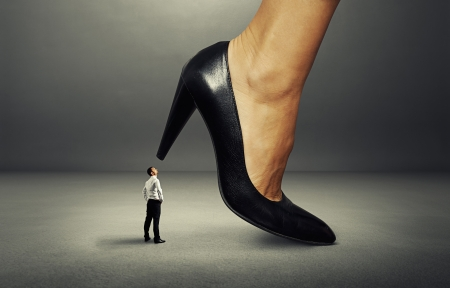 dominate: concept photo of businessman under supervision of boss woman
