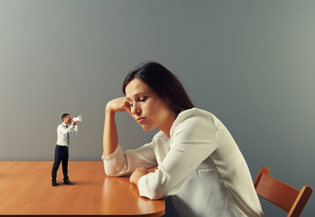 human voice: small man urge on tired businesswoman Stock Photo