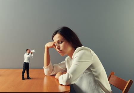 dismal: small man urge on tired businesswoman Stock Photo