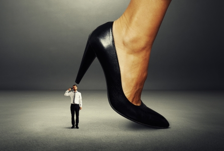 small man with gun under big female heel photo