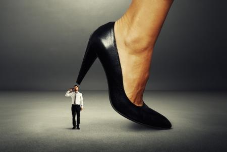 small man with gun under big female heel Stock Photo - 22087678