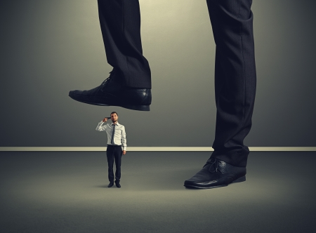 aggressive people: small desperate businessman with gun under big leg his boss Stock Photo