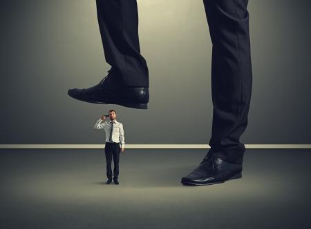 downtrodden: small desperate businessman with gun under big leg his boss Stock Photo