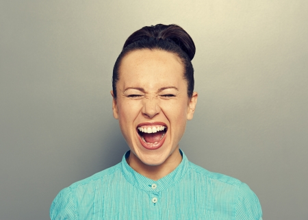 hysterics: screaming young girl over grey background