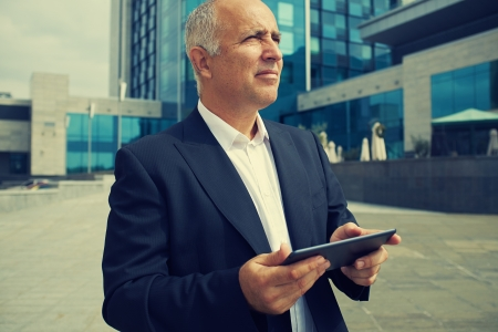touchpad: senior businessman holding touchpad and looking up