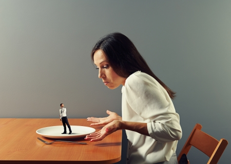 disillusionment: small man go away from plat, big woman looking at him Stock Photo