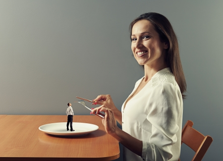 beautiful young woman ready to eat small man photo