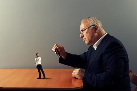 zvětšovací sklo: vyděšený pracovník pod lupou jeho šéf