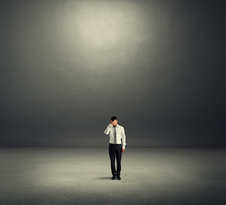unsuccessful: sad businessman in dark room Stock Photo