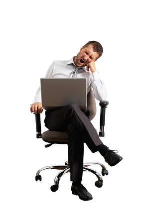 despondency: tired businessman sitting on office chair and yawning