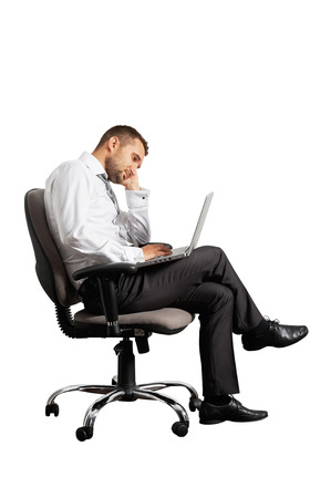 despondency: tired businessman sitting on office chair and looking at laptop