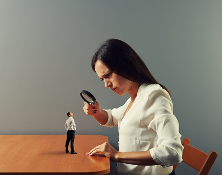 big and small: serious businesswoman looking with magnifying glass at small man Stock Photo