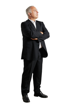 senior business: serious businessman standing in the studio and looking up Stock Photo