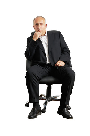 thoughtful senior man sitting on office chair and looking at camera photo