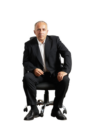 isolated chair: serious businessman sitting on office chair and looking at camera. isolated on white background