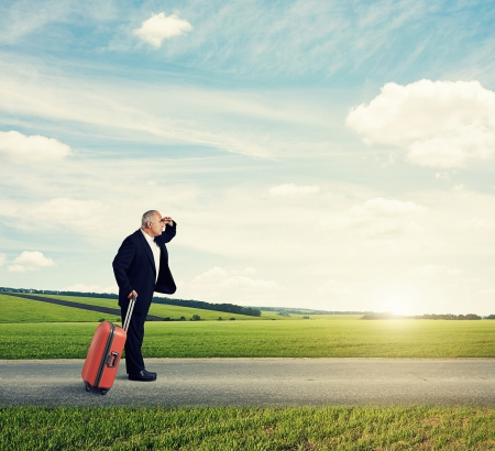 senior man standing on the road, holding suitcase and looking forward