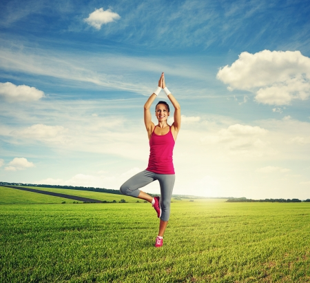 smiley young woman practicing yoga at outdoor photo