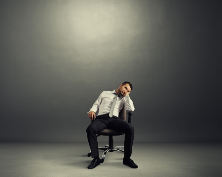 lazybones: bored businessman sitting in the empty dark room Stock Photo