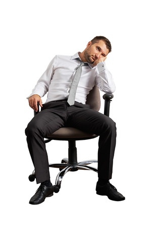 tedious: bored businessman sitting on the office chair. isolated on white background