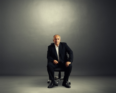 serious businessman sitting on the office chair and looking at camera photo