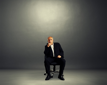 pensive businessman sitting on office chair and looking at camera photo