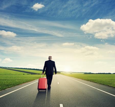 senior man met koffer en lopen op de weg