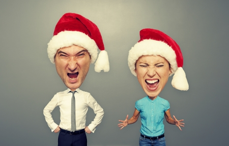 emotional bighead couple in santa hat over dark background photo