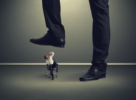 downtrodden: scared small man under big leg Stock Photo