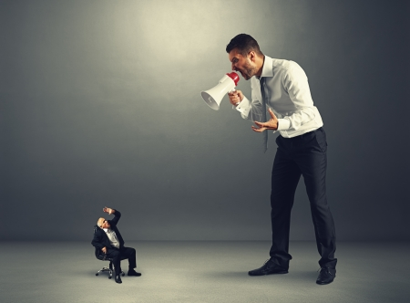 jonge baas schreeuwt tegen hooggeplaatste werknemer Stockfoto