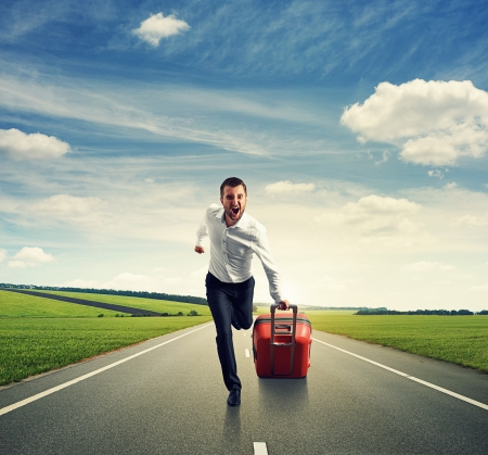 screaming man with suitcase running on the road photo