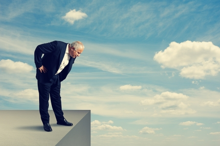 man looking down: senior businessman standing over the precipice and looking down