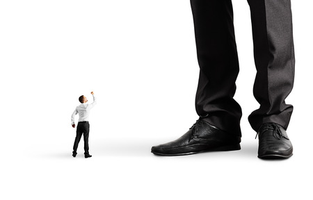 big and small: small angry businessman looking up and showing fist to his big boss. isolated on white background Stock Photo