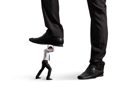 downtrodden: small businessman under big leg his boss. isolated on white background Stock Photo