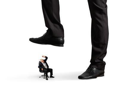 scared senior businessman under big leg his boss. isolated on white background photo