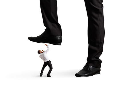 scared small businessman under big leg his boss. isolated on white background photo