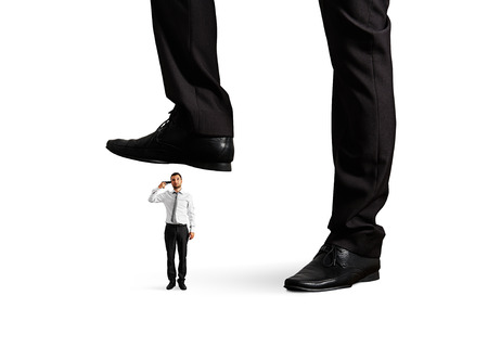 small desperate businessman with gun under big leg his boss. isolated on white background photo