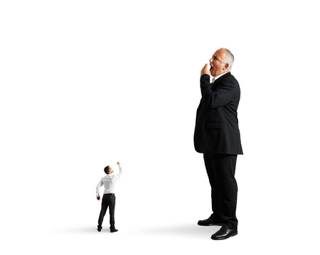 small man showing fist to big bored businessman. isolated on white background photo