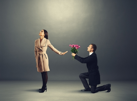 young beautiful woman dont looking at man with flowers photo