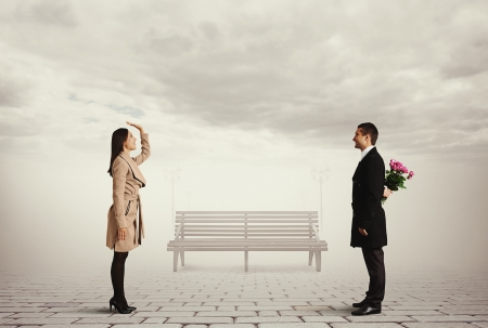 smiley beautiful woman greeting man with flowers photo
