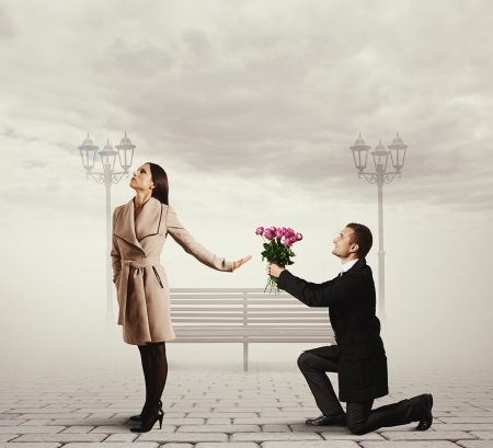angry young woman rejecting man with flowers photo