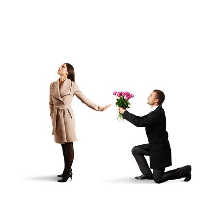 jonge mooie vrouw tot afwijzing man met bloemen. geïsoleerd op witte achtergrond