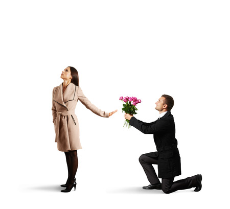young beautiful woman rejecting man with flowers. isolated on white background photo