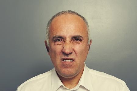 discredit: discontented senior man over dark background