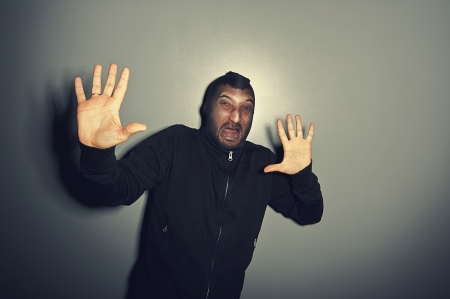 remonstrance: criminal man screaming and raising hands up over grey background