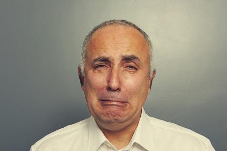 cry: portrait of sorrowful senior man over grey