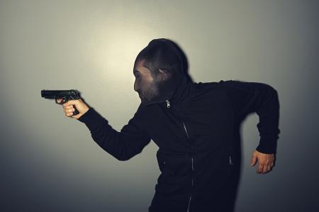 slink: thief with gun stealing over dark wall